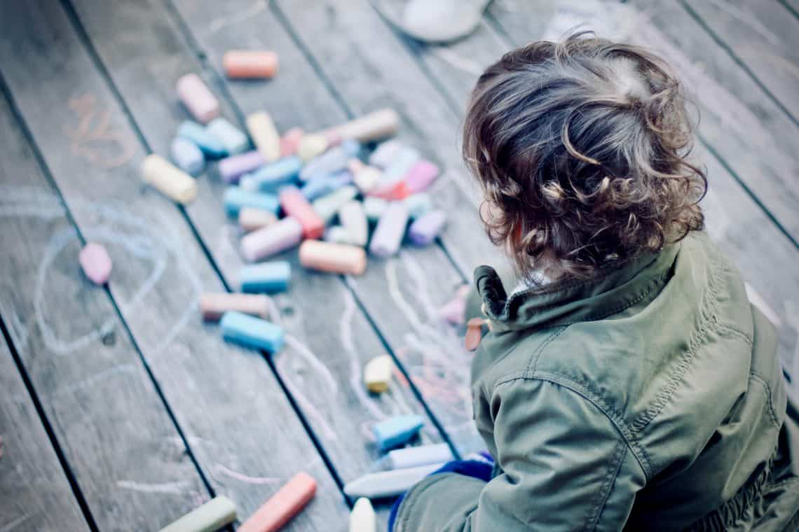 Child learning how to keep busy at home with sidewalk chalk.