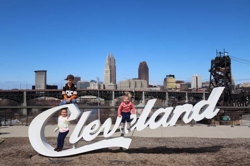 Three kids posing on a Cleveland sign while on a road trip