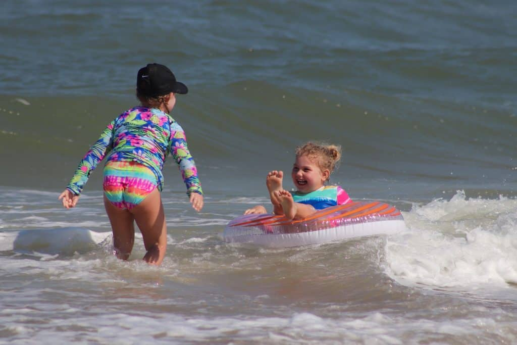 Two kids playing in the ocean after a long road trip
