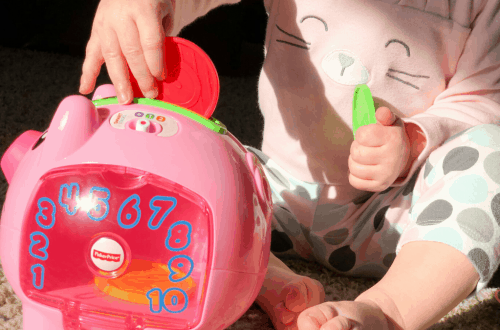 Toddler putting coins into piggy bank STEM toy