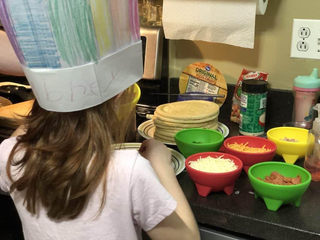 Child topping a personal pizza