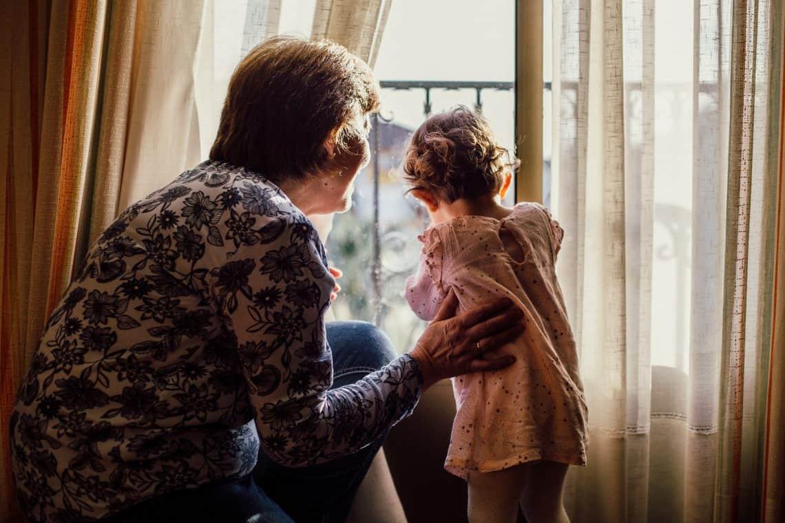 Grandma with grandchild near window