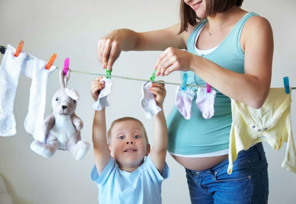 Little boy helping hang laundry with his mother who is having a second baby.