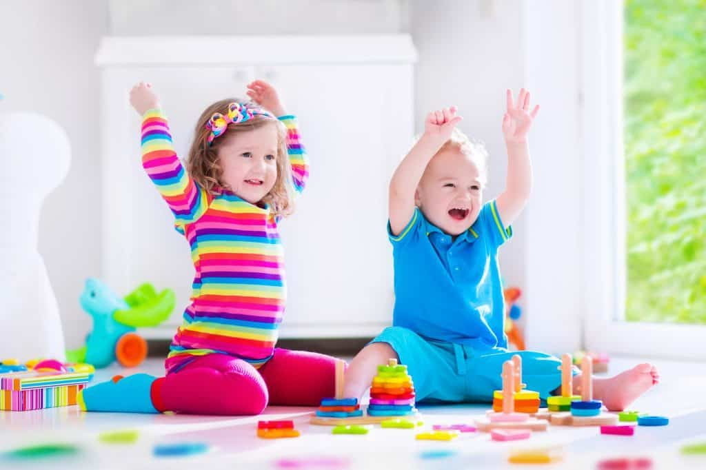 Two kids being entertained by playing with blocks on the floor.