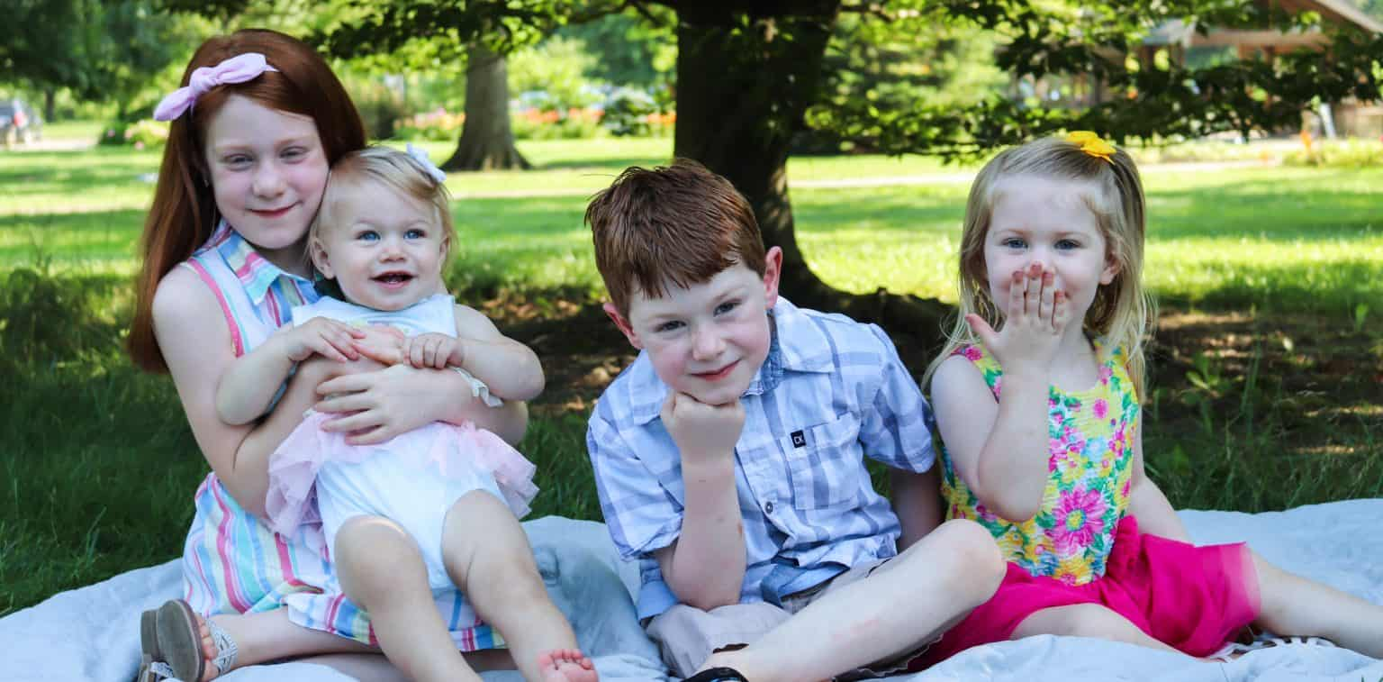 Four kids sitting together in front of some trees