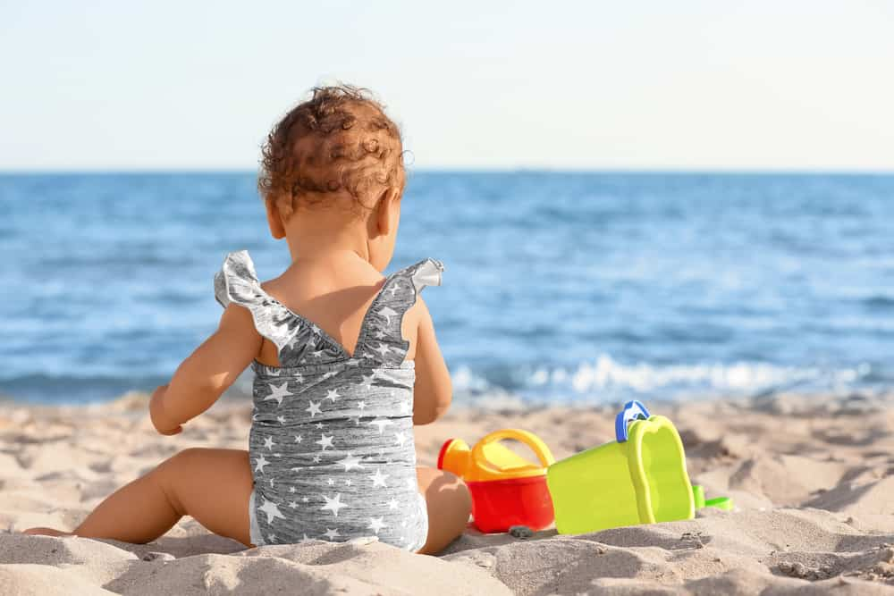 Toddler playing with beach toys for toddlers in the sand