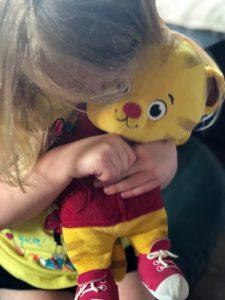 Child hugging Daniel Tiger stuffed animal