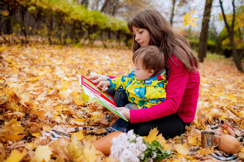 Mom and child reading a fall book for toddlers while sitting in autumn leaves.