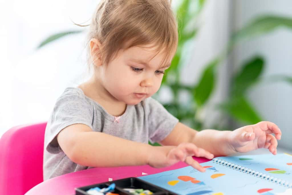 Toddler playing with reusable sticker book