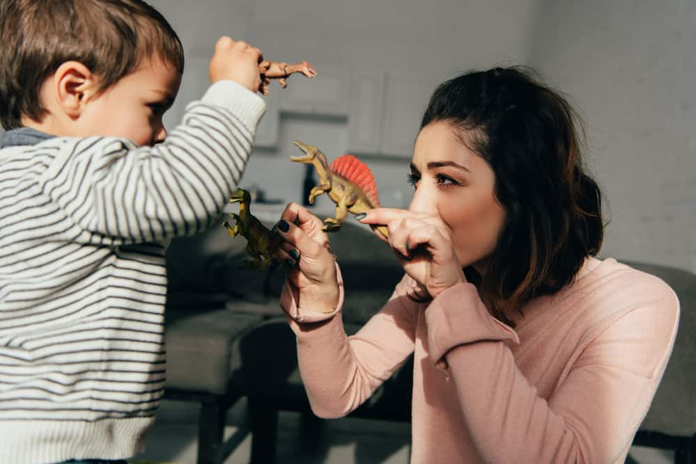 Mom and toddler playing with dinosaur toys