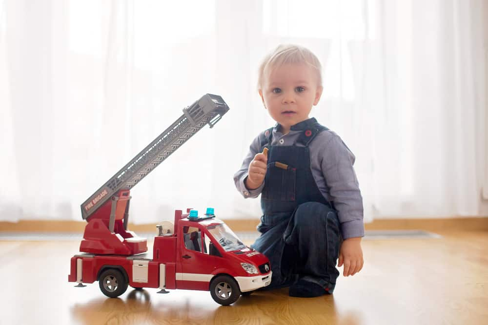 Toddler playing with a fire truck toy