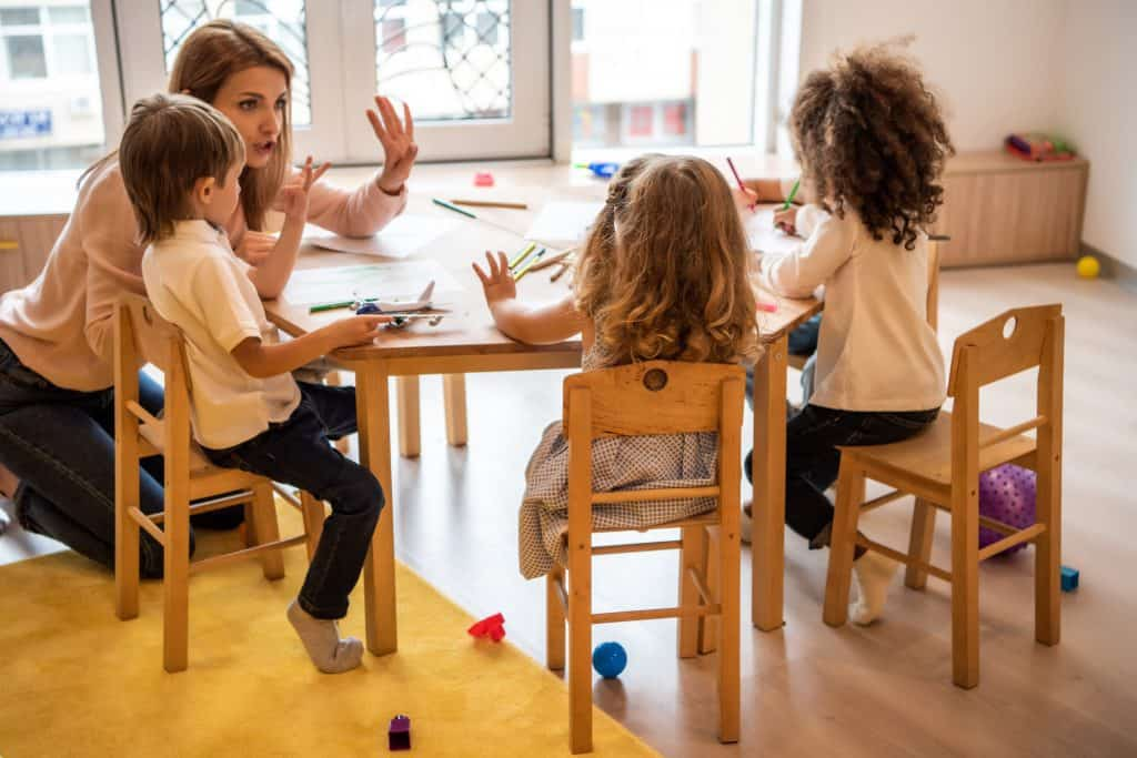 In-home daycare provider working with young children at a table.