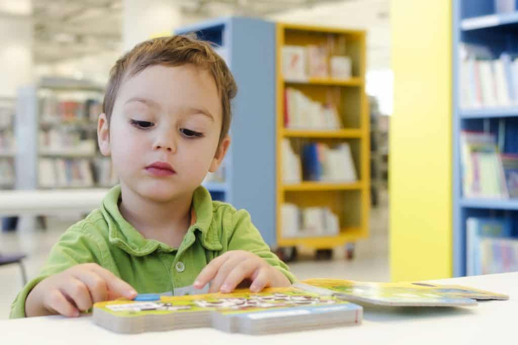 Toddler reading interactive book at a table in the library